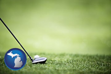 a golf ball and a golf club on a golf course - with Michigan icon